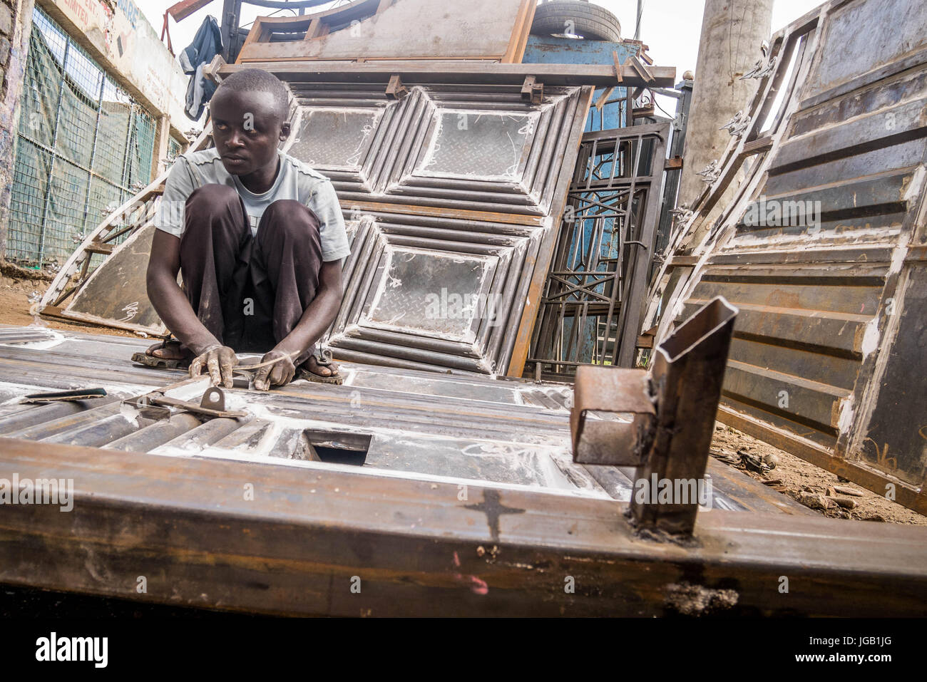 Nairobi, Kenya - December 2, 2016: Worker at welding workshop using sandpaper - Stock Image