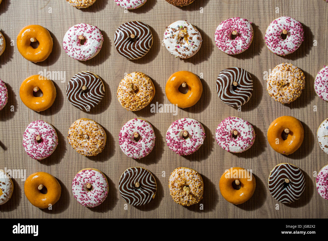 Delicious , colorful doughnuts in a row - Stock Image