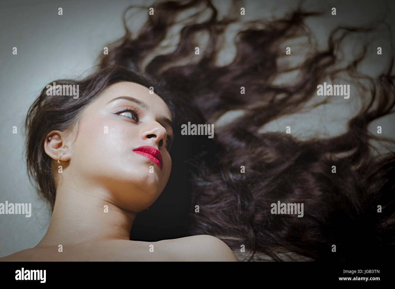 concept shoot with a beautiful Indian model with long hair at a studio - Stock Image