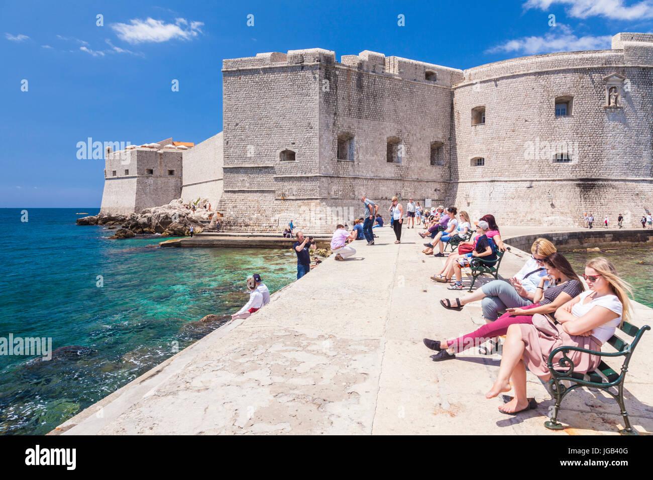 Croatia Dubrovnik Croatia Dalmatian coast tourists sitting on the sea wall Arsenal St John Fort dubrovnik old harbour - Stock Image