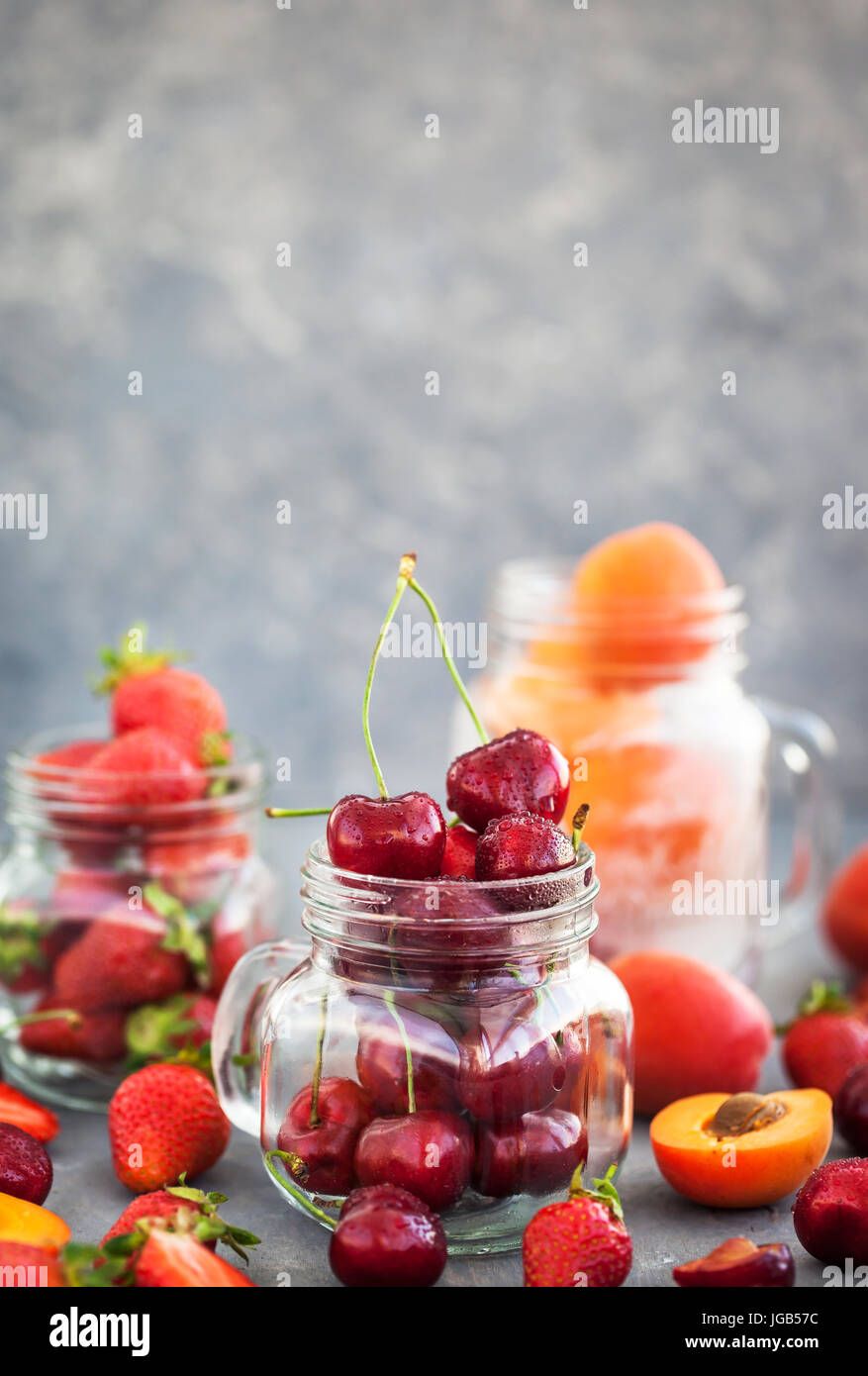 Fresh ripe summer cherry, strawberry and apricots in glass mason jars - Stock Image