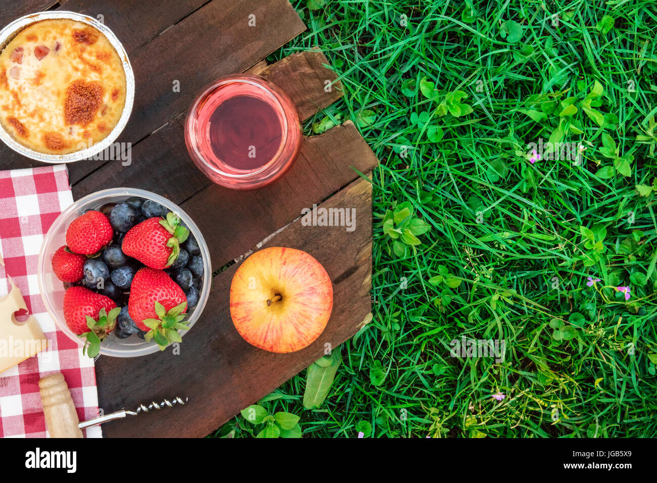Picnic food and rose wine on green grass with copyspace - Stock Image
