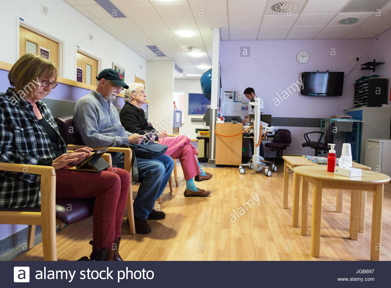 NHS Hospital patients waiting in an outpatient clinic hospital waiting room, John Radcliffe Hospital, Oxford England - Stock Image