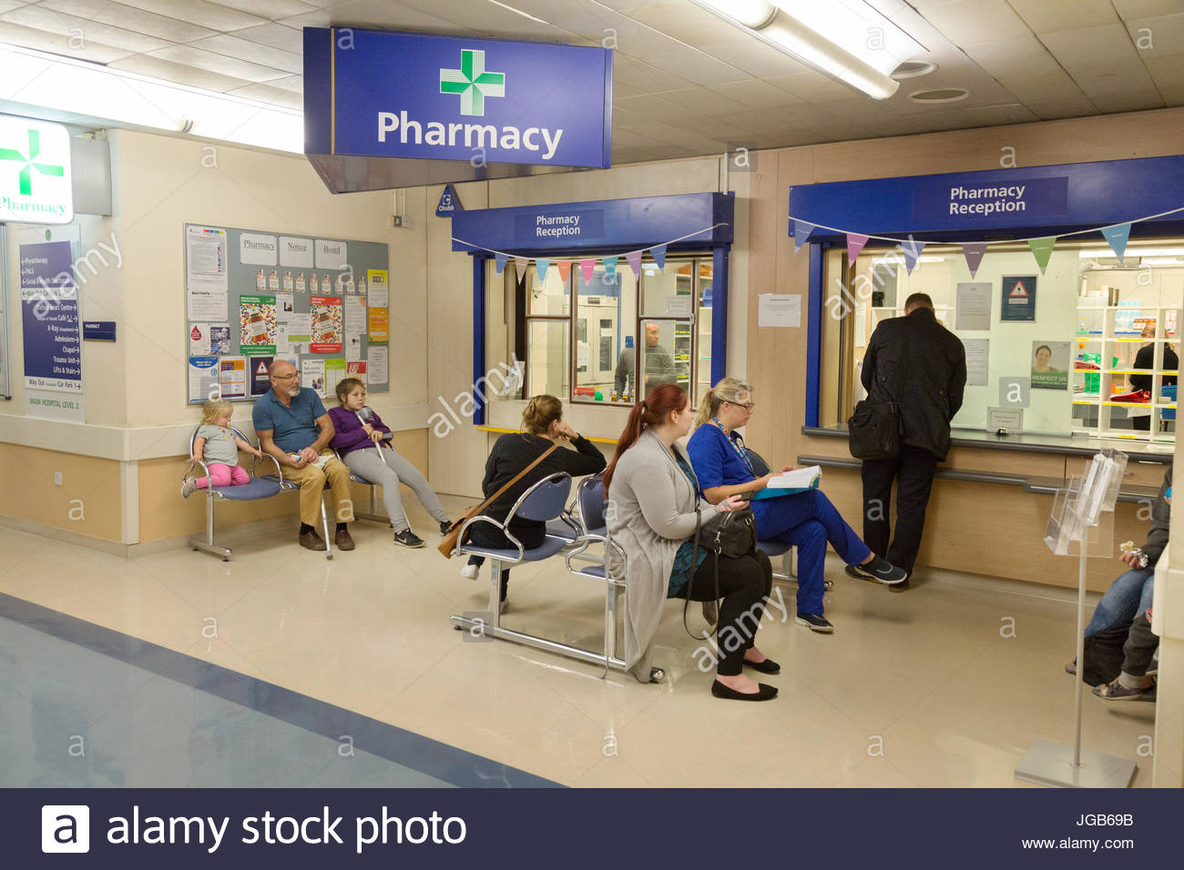 Hospital Pharmacy - patients waiting to collect medication, the Hospital Pharmacy, John Radcliffe Hospital, Oxford - Stock Image