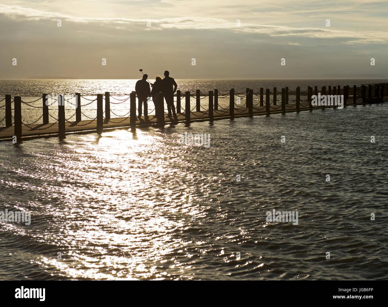 Three people taking selfie on walkway between sea and Marine Lake, Weston-super-Mare, Somerset, England UK - Stock Image