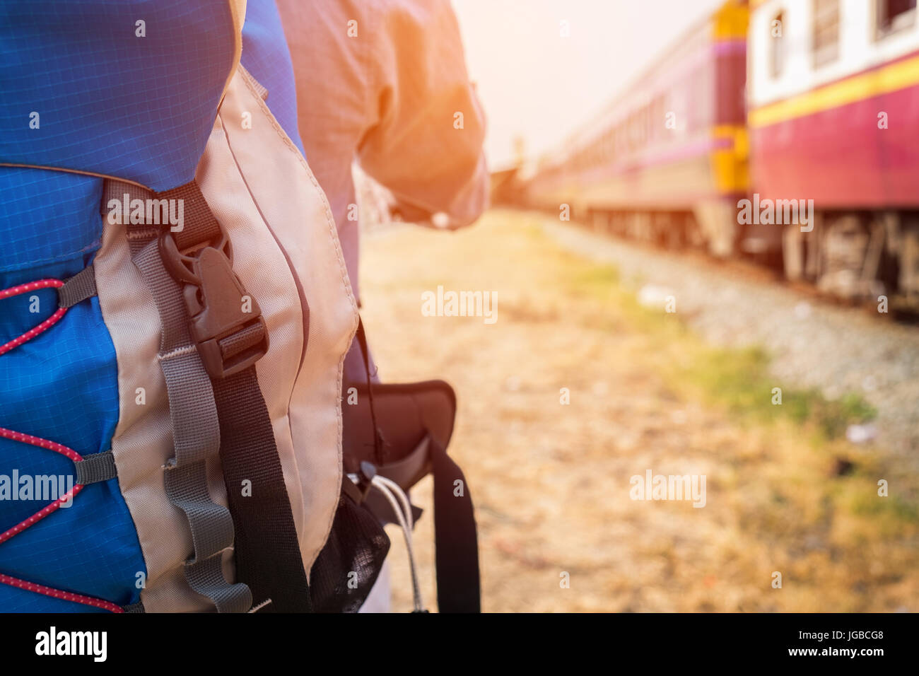 Young hipster man with a backpack ready to embark on a journey by train, Trendy guy standing looking away. - Stock Image