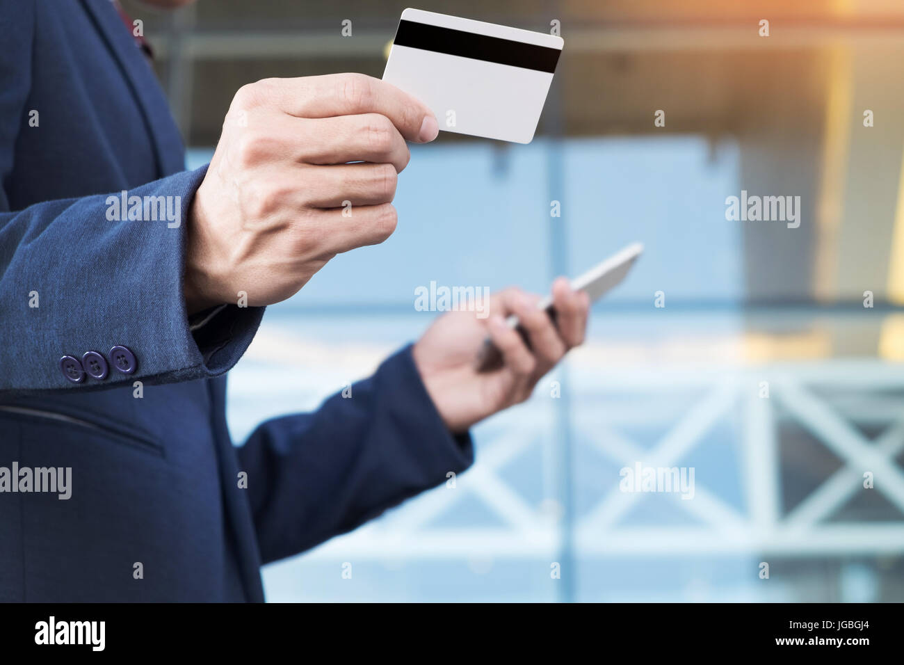 Handsome male owner of trading company dialing number from visit card on his modern smartphone searching skill specialist - Stock Image