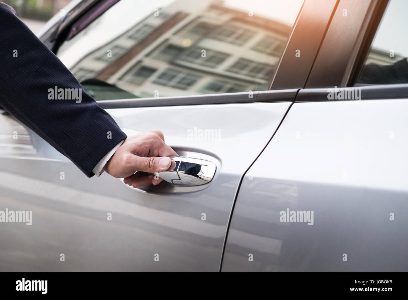 Chauffeur s hand on handle. Close-up of man in formal wear opening a passenger car door. Stock Photo