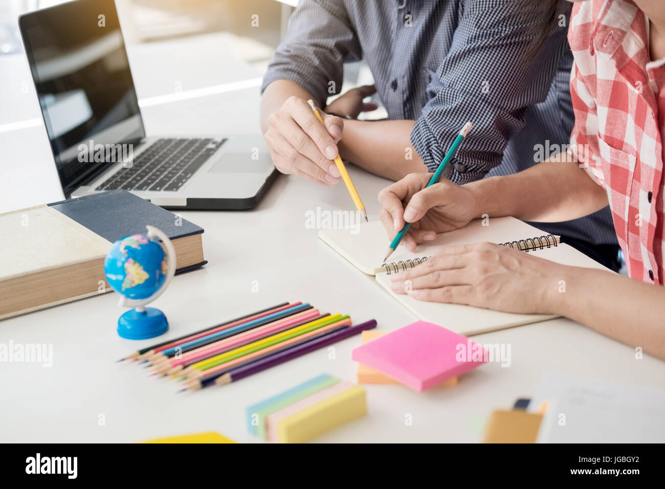 Young woman and man studying for a test/ an exam. Tutor books with friends. Young students campus helps friend catching - Stock Image