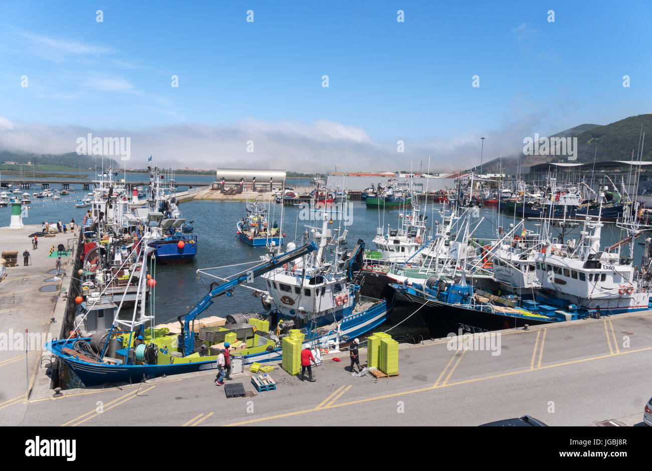 Fishermen at work on fishing boat in Santoña harbour, Cantabria, Spain - Stock Image