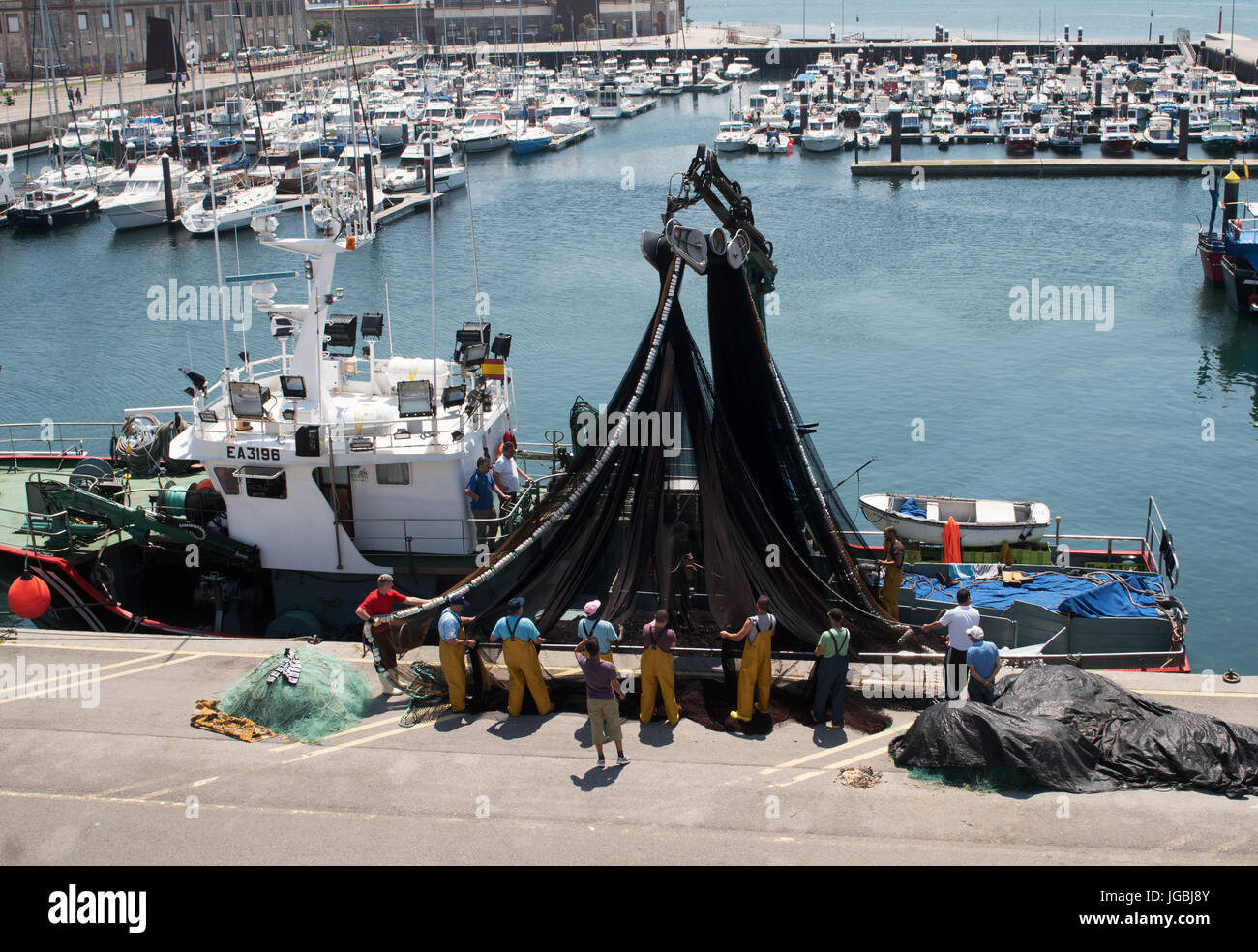 Fishermen inspecting nets on fishing boat in Santoña harbour, Cantabria, Spain - Stock Image