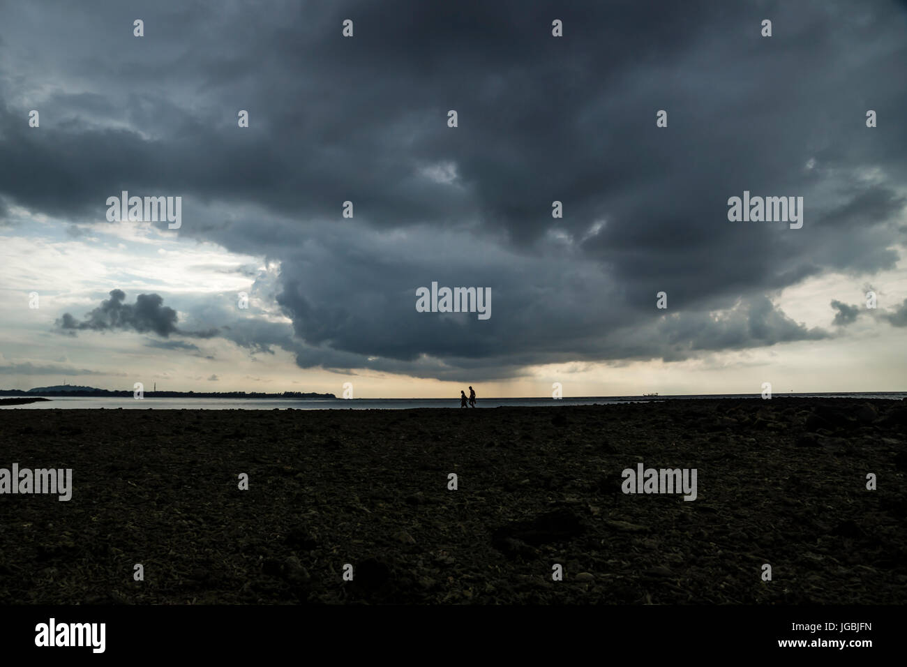 People walking on coral scrap under massive cloud in Gili Air, Lombok, Indonesia - Stock Image