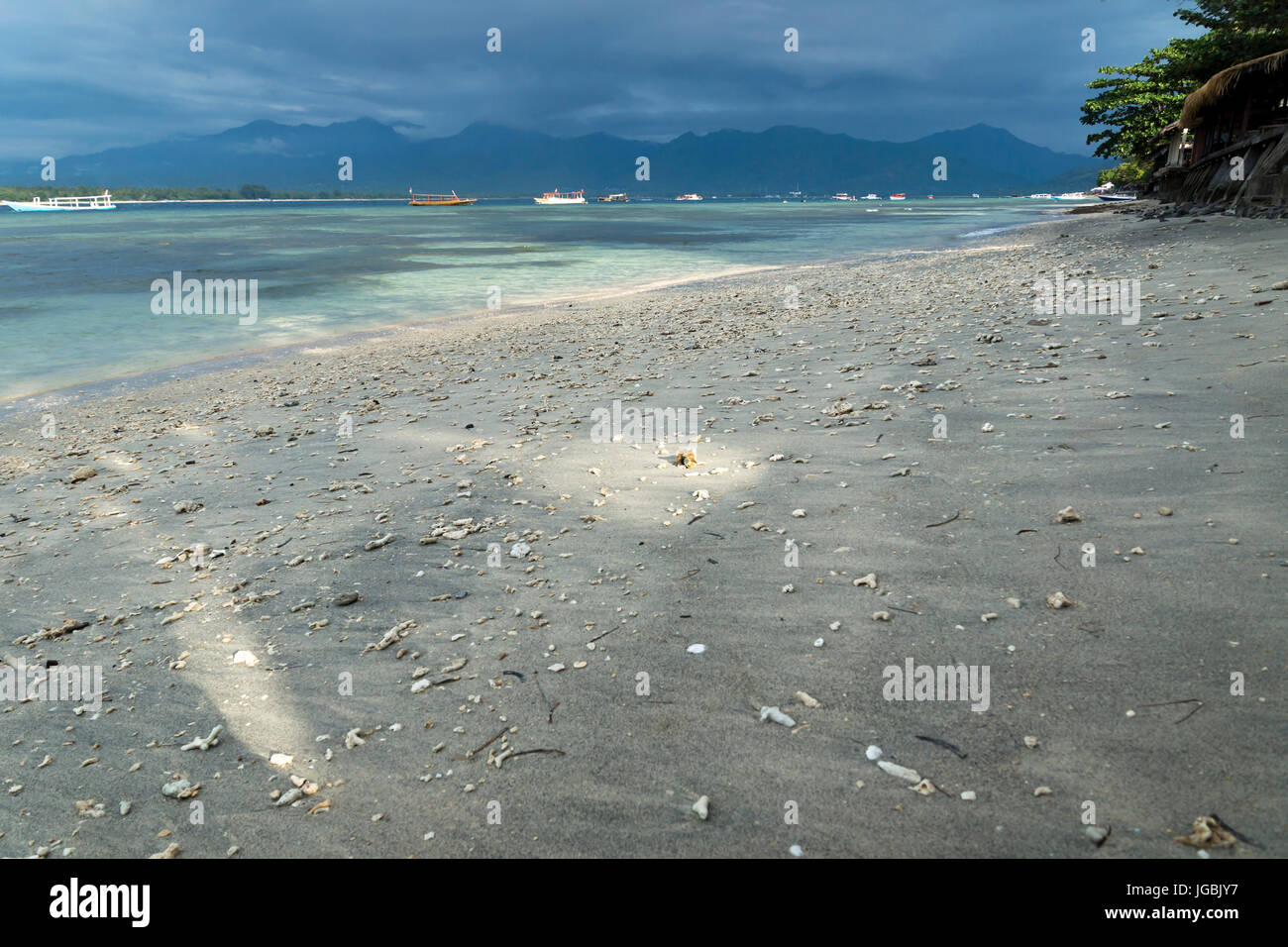 VIew to Lombok mountains from the sunny beach of Gili Air during sunset, Indonesia - Stock Image