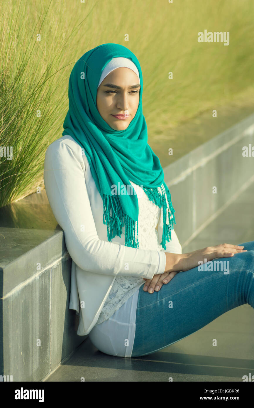 Serious young Muslim woman wearing hijab sitting outdoors looking away - Stock Image