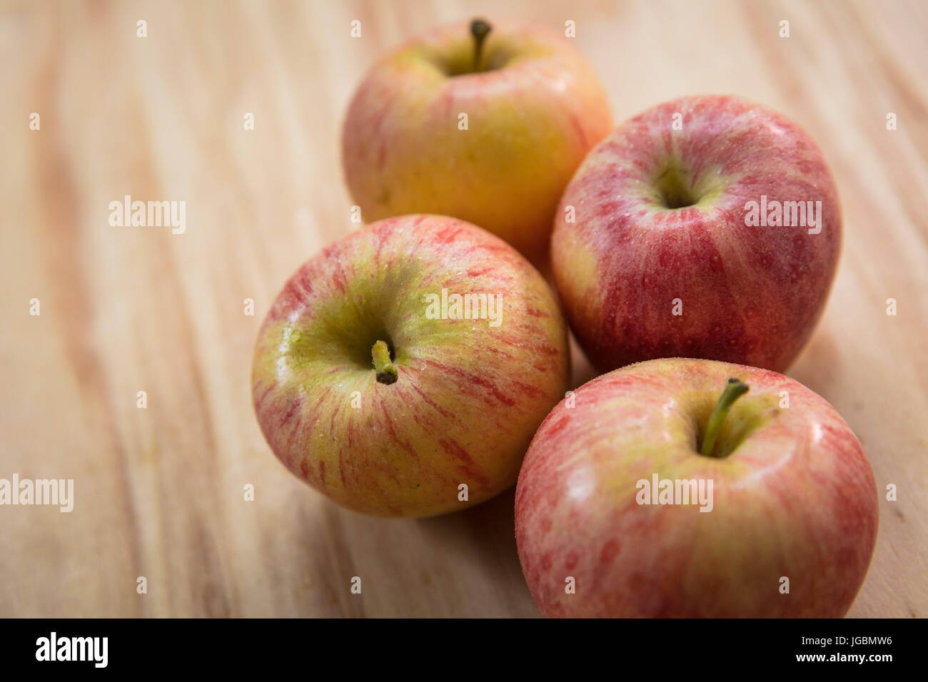 four apples on a wooden surface pink lady variety stock photo