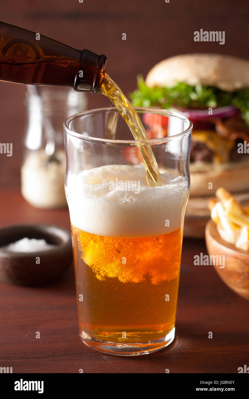 pouring india pale ale beer into pint glass and fast food - Stock Image