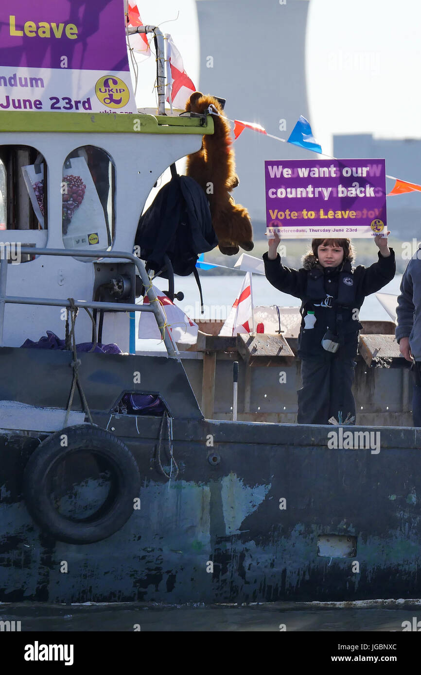 Boy holding up poster on board a fishing boat. The slogan says, we want our country back during the EU referendum - Stock Image