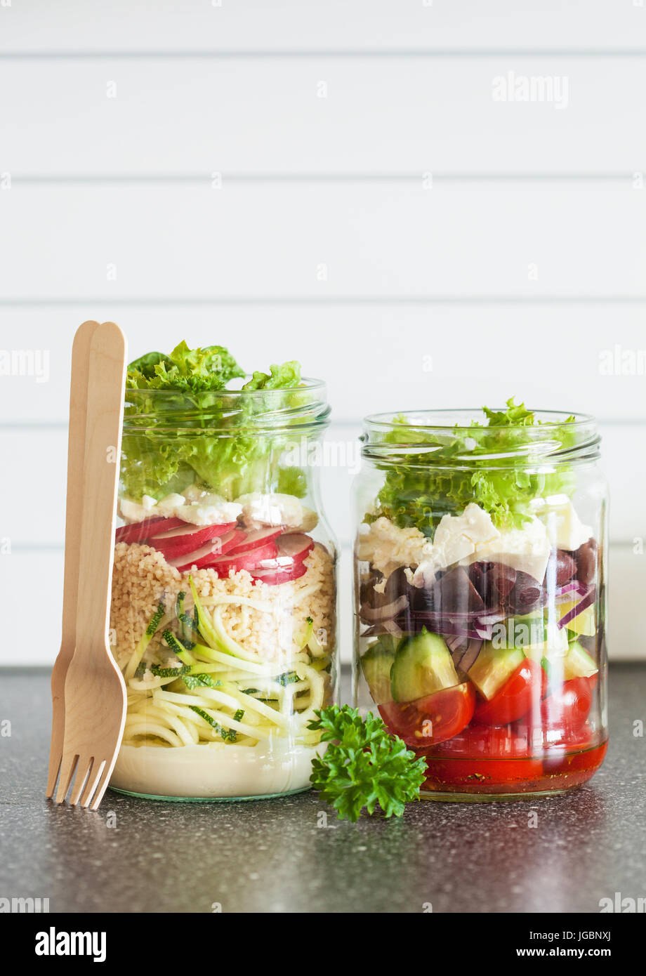 healthy vegetable and cheese salad in mason jars - Stock Image