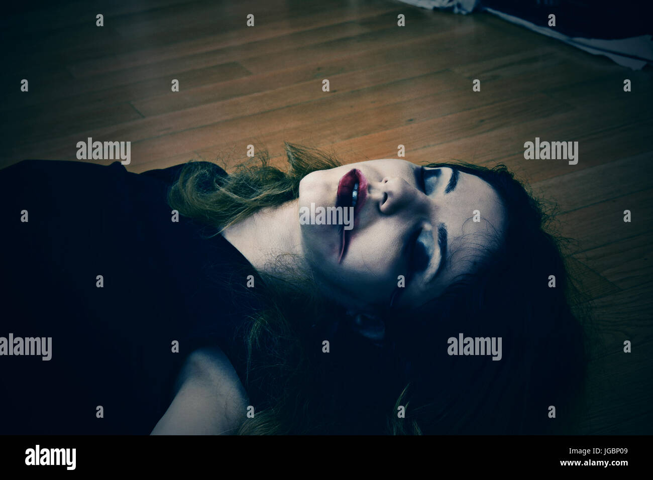 Dead girl on the floor with blood from her mouth and nose - Stock Image