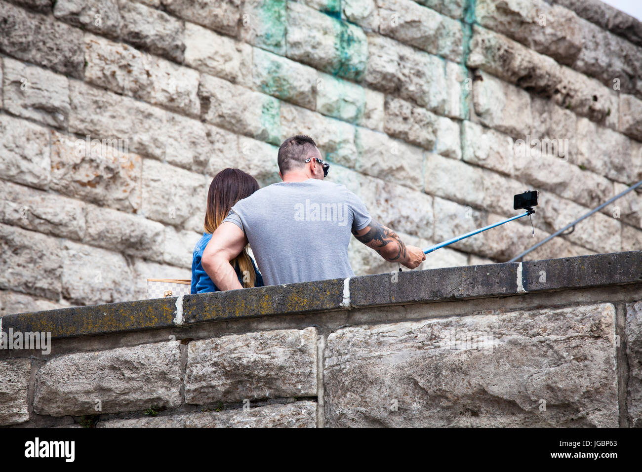 Germany, Cologne, a couple takes pictures of themselves with a selfie stick at the Hohenzollern bridge in the district - Stock Image