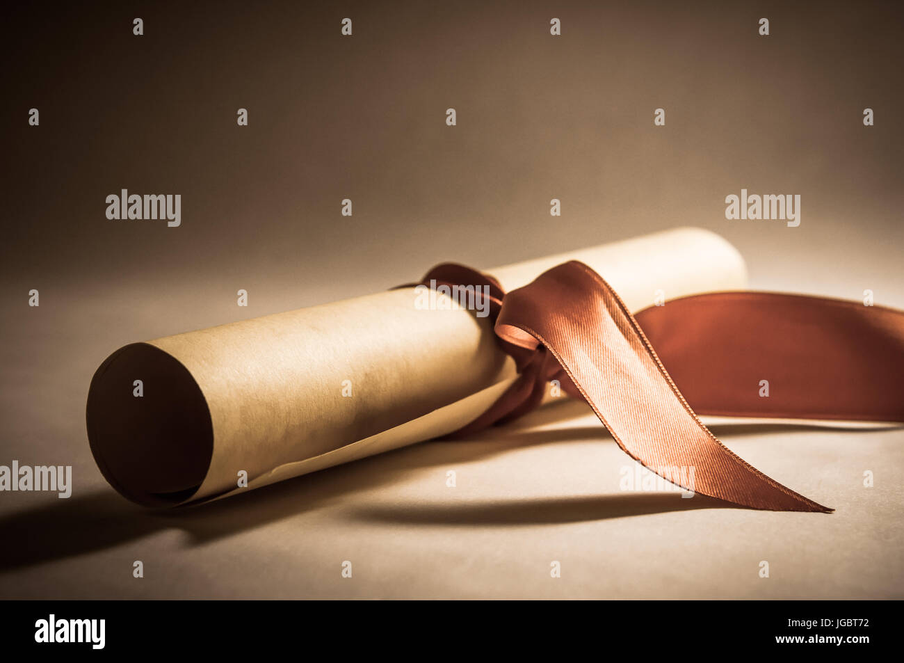 A parchment diploma scroll, rolled up with red ribbon laid at an oblique angle.  Processed to give a vintage or - Stock Image