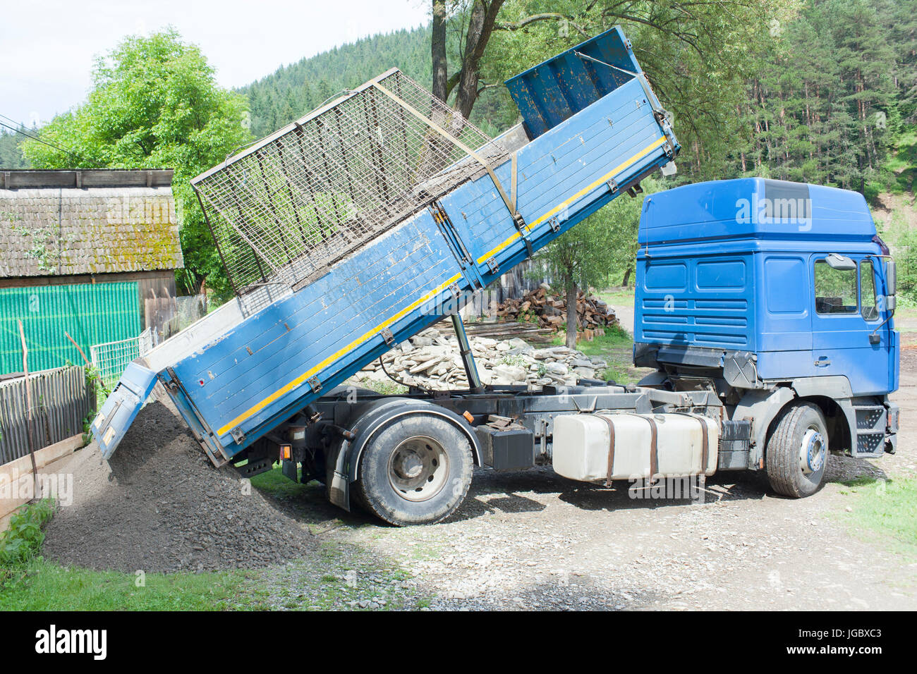 truck dumping ground with hydraulic tilt - Stock Image