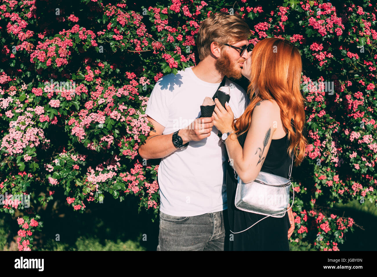 Couple in park eating ice cream cones - Stock Image