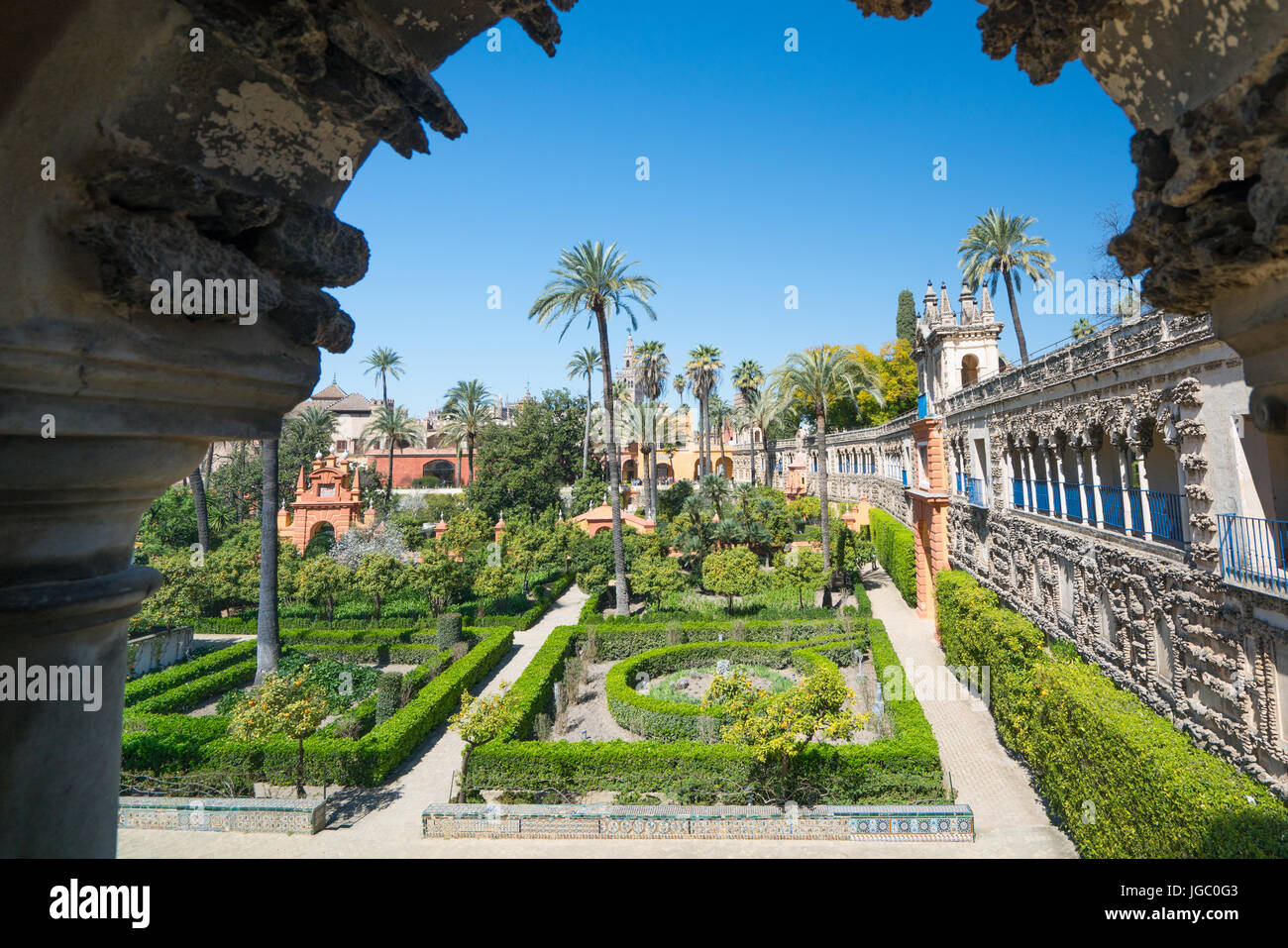 Gardens of the Alcazar, Seville, Andalucia, Spain framed by an open stone archway Stock Photo
