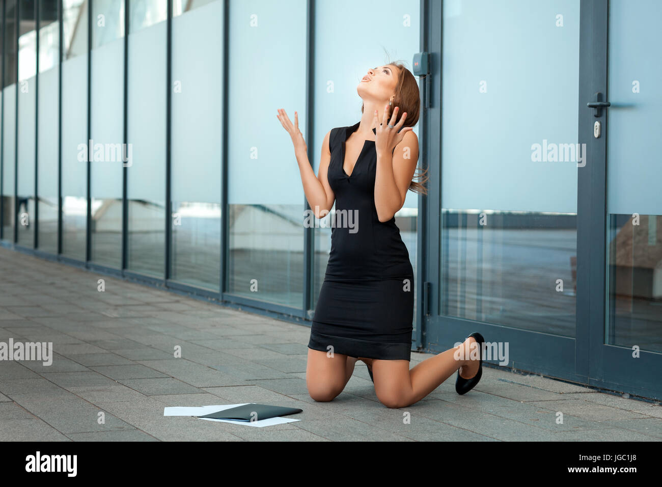 Girl knelt down and rejoices. Near scattered documents. - Stock Image