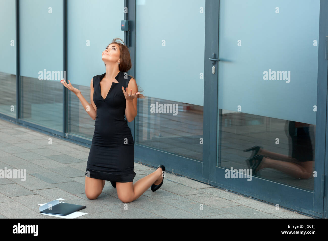 Girl kneels in front of the office. It's pretty smiles. - Stock Image