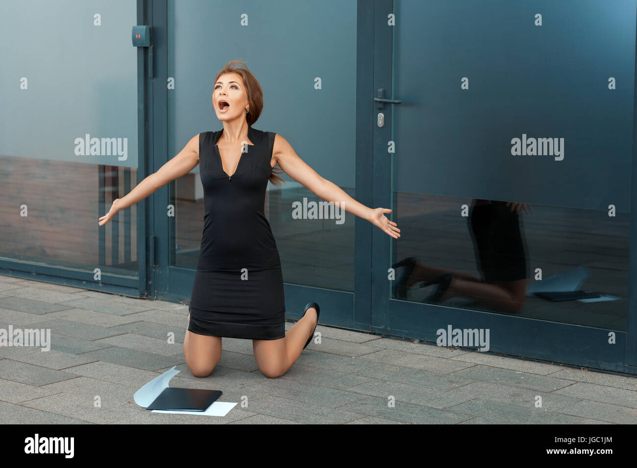 Beautiful girl on her knees and screaming for joy. Nearby lies the contract. - Stock Image