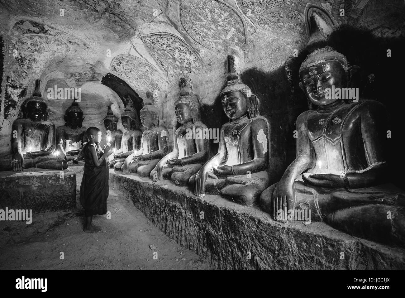 Monk praying with candle light at Po Win Taung / Hpowindaung cave - Monywa - Sagaing region - Northern Myanmar Stock Photo
