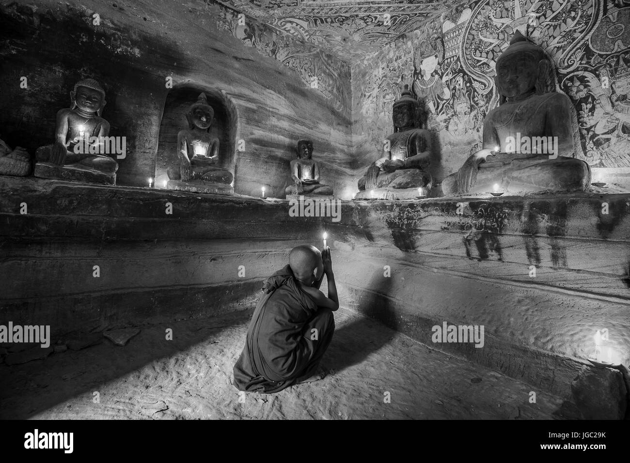 Monk praying with candle light at Po Win Taung / Hpowindaung cave - Monywa - Sagaing region - Northern Myanmar - Stock Image