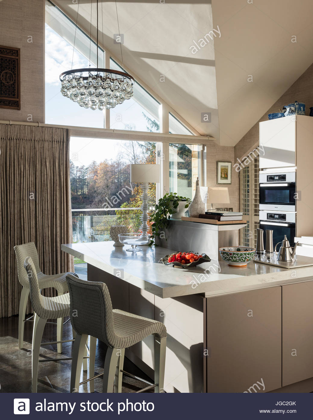 Lightbulb pendant above breakfast bar in A-frame kitchen with lakeside view - Stock Image