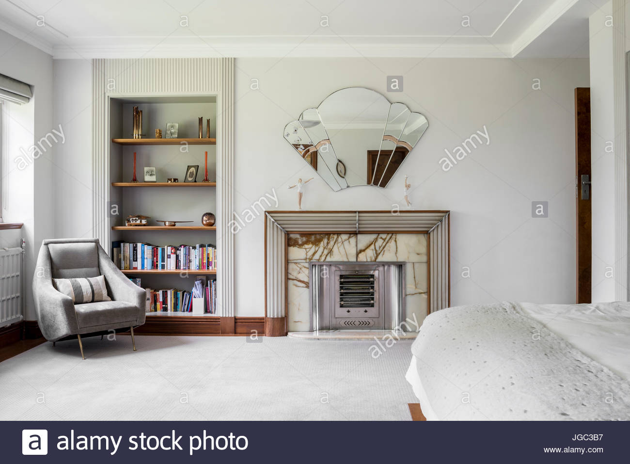 Light grey armchair and bookshelves beside Art Deco fireplace and ...
