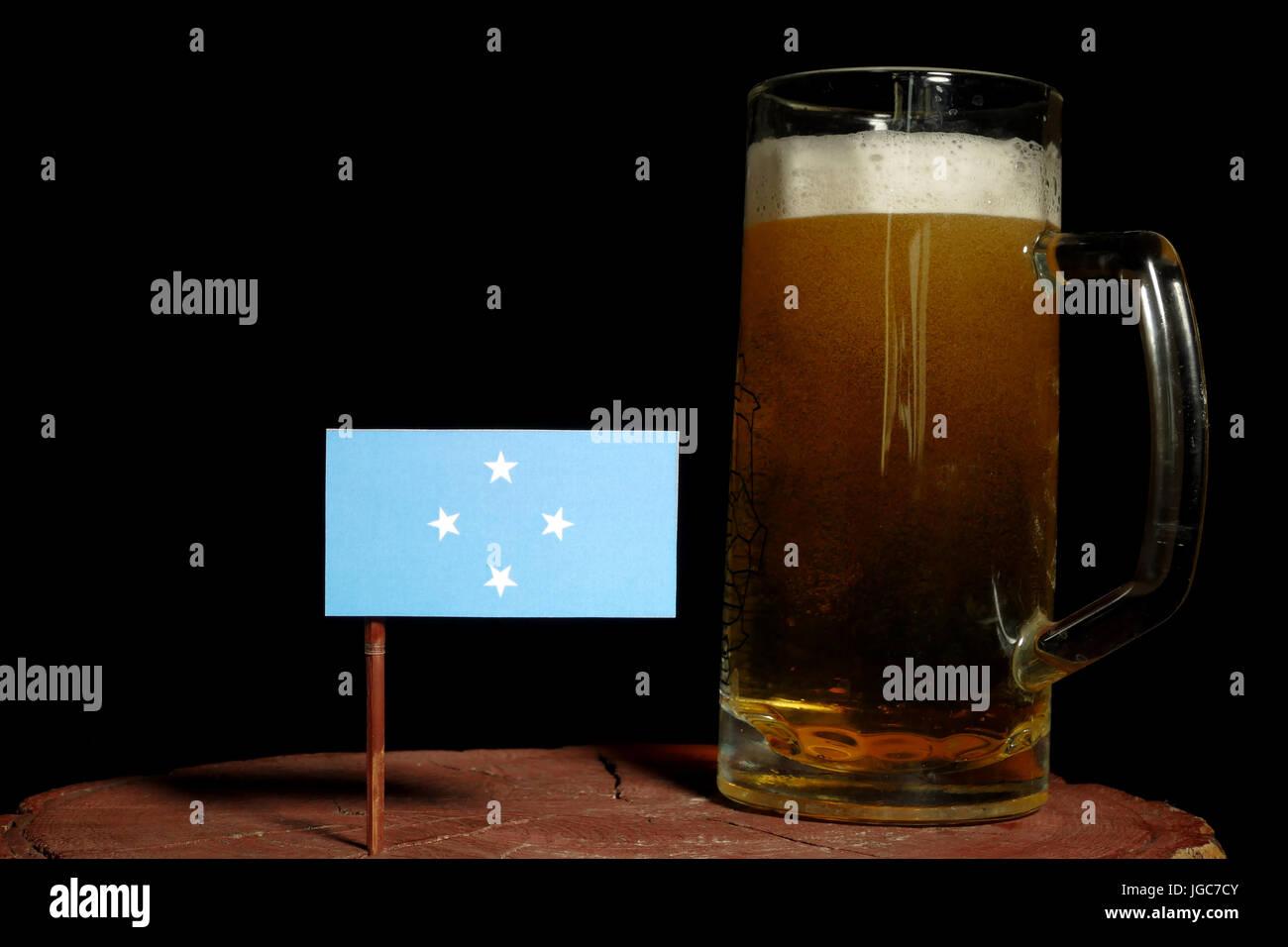 Micronesian flag with beer mug isolated on black background - Stock Image