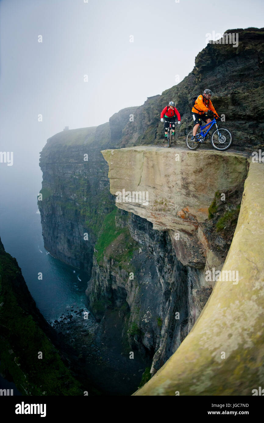 Professional mountain bikers Hans Rey and Steve Peat riding the Cliffs of Moher - Stock Image