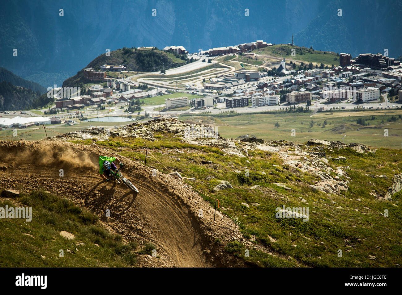 A mountain biker on a dusty Alpine trail, with ski village in background - Stock Image