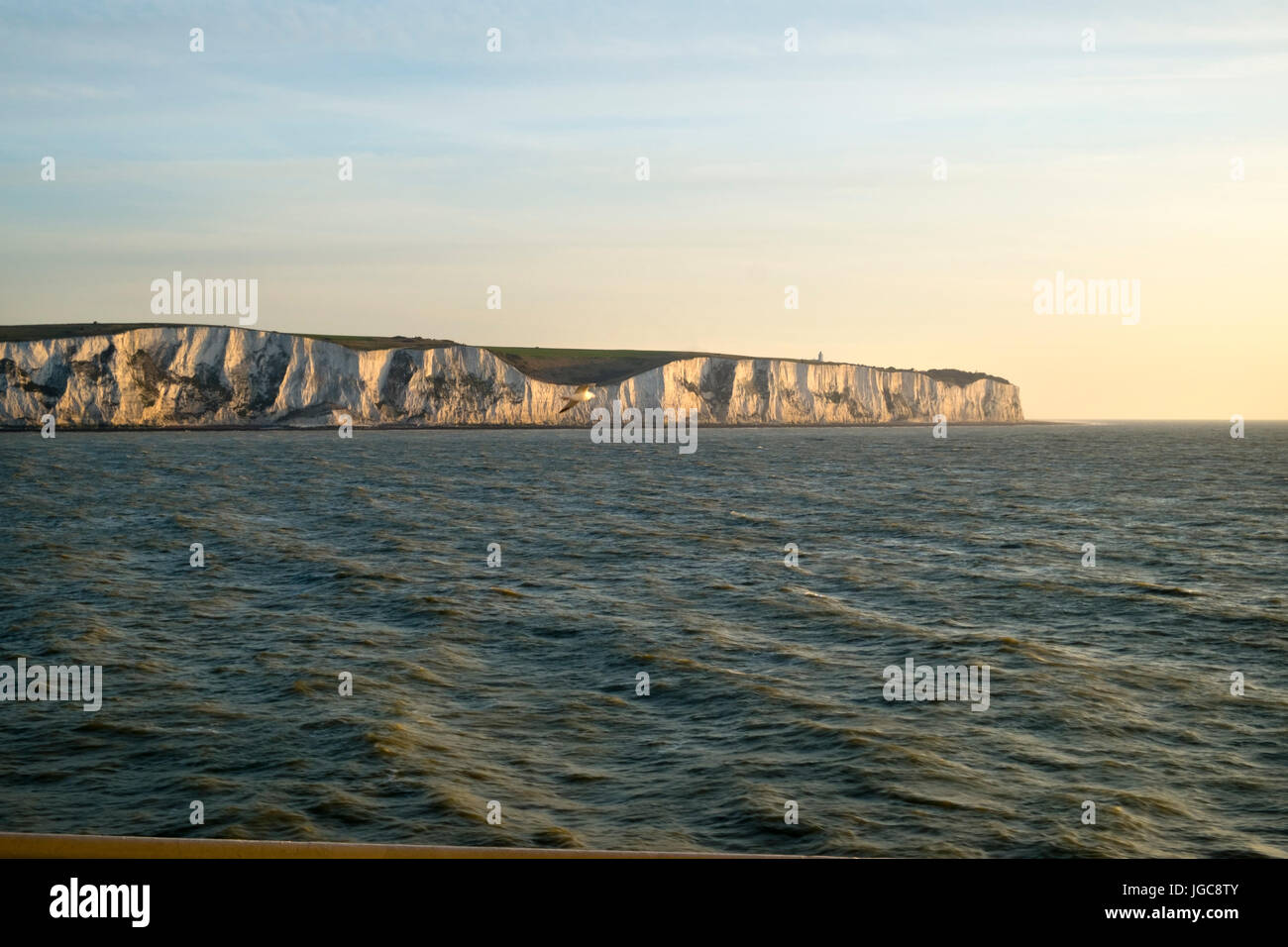 An early morning cross channel ferry passes the white cliffs of Dover, Kent, UK heading for Calais, France. - Stock Image