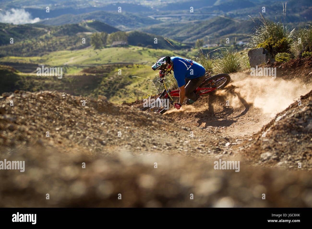A downhill mountain bike rider slides his bicycle through a corner on a purpose built dusty trail in Andalucia, - Stock Image