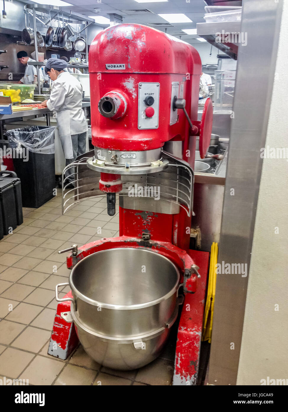 Genial Large Red Industrial Mixer With An Empty Clean Stainless Steel Bowl In A  Bakery With People Working At Kitchen Counters In The Background