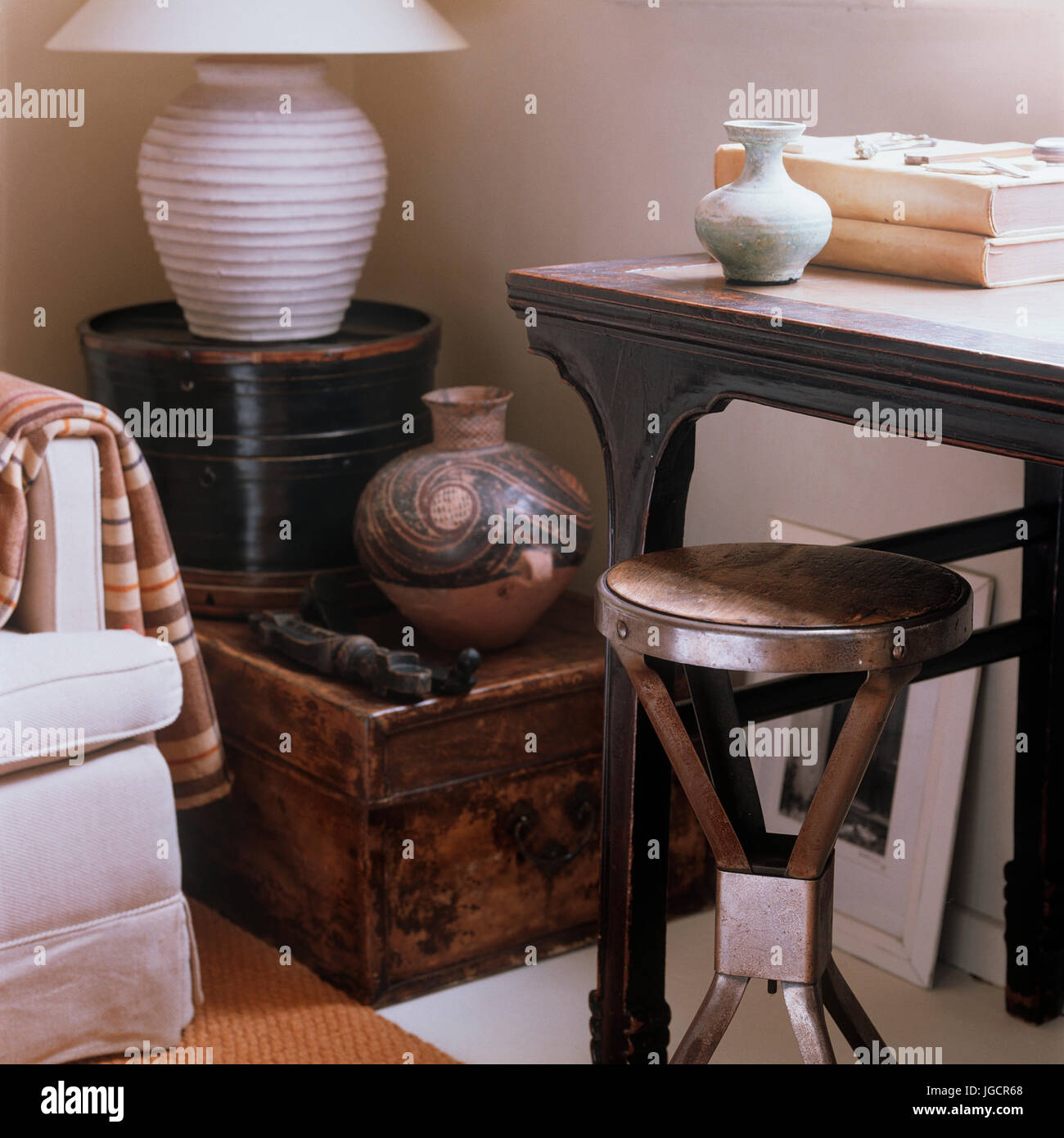 Wooden stool and table by lamp - Stock Image