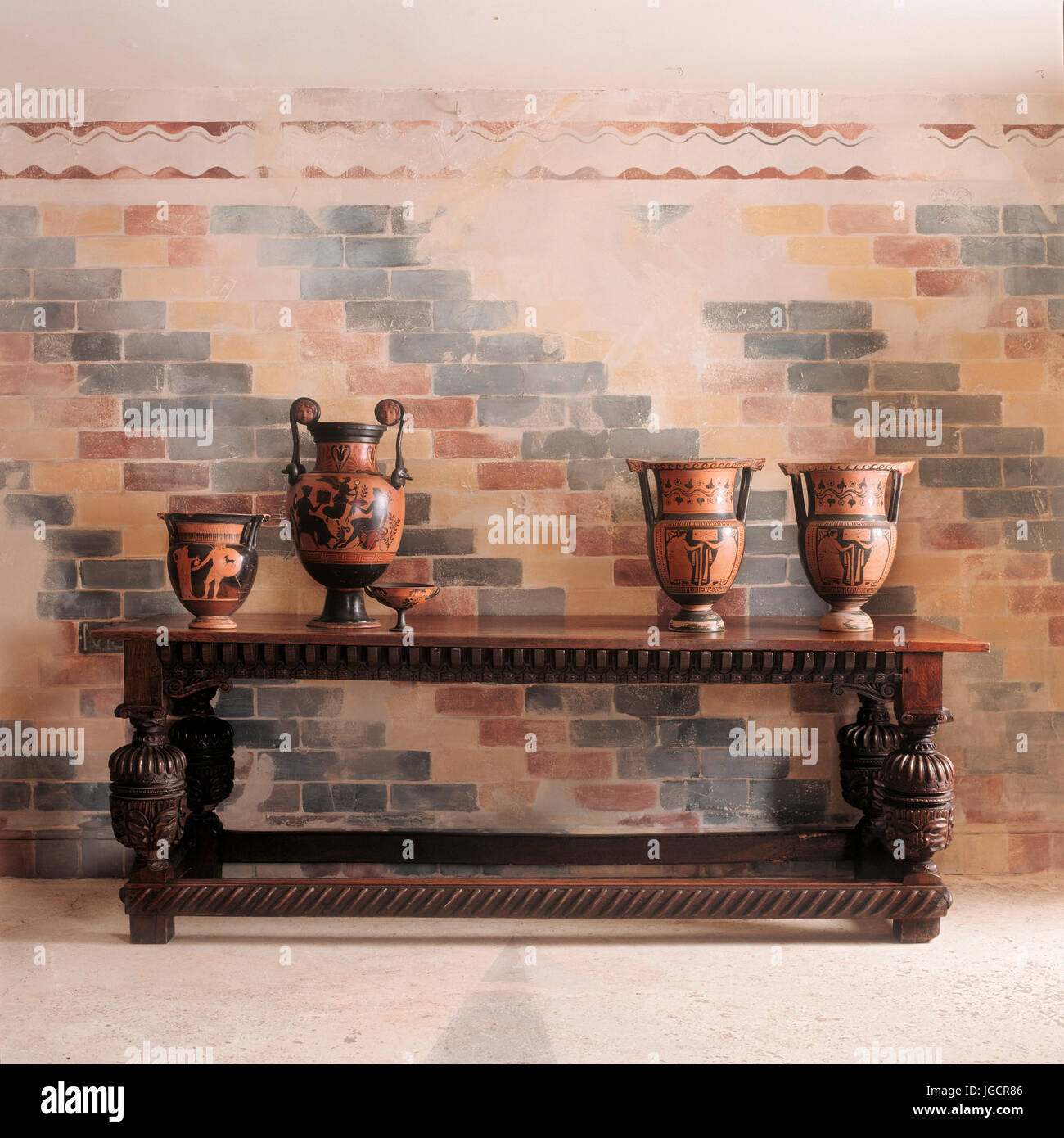 Vases on wooden table by brick wall - Stock Image