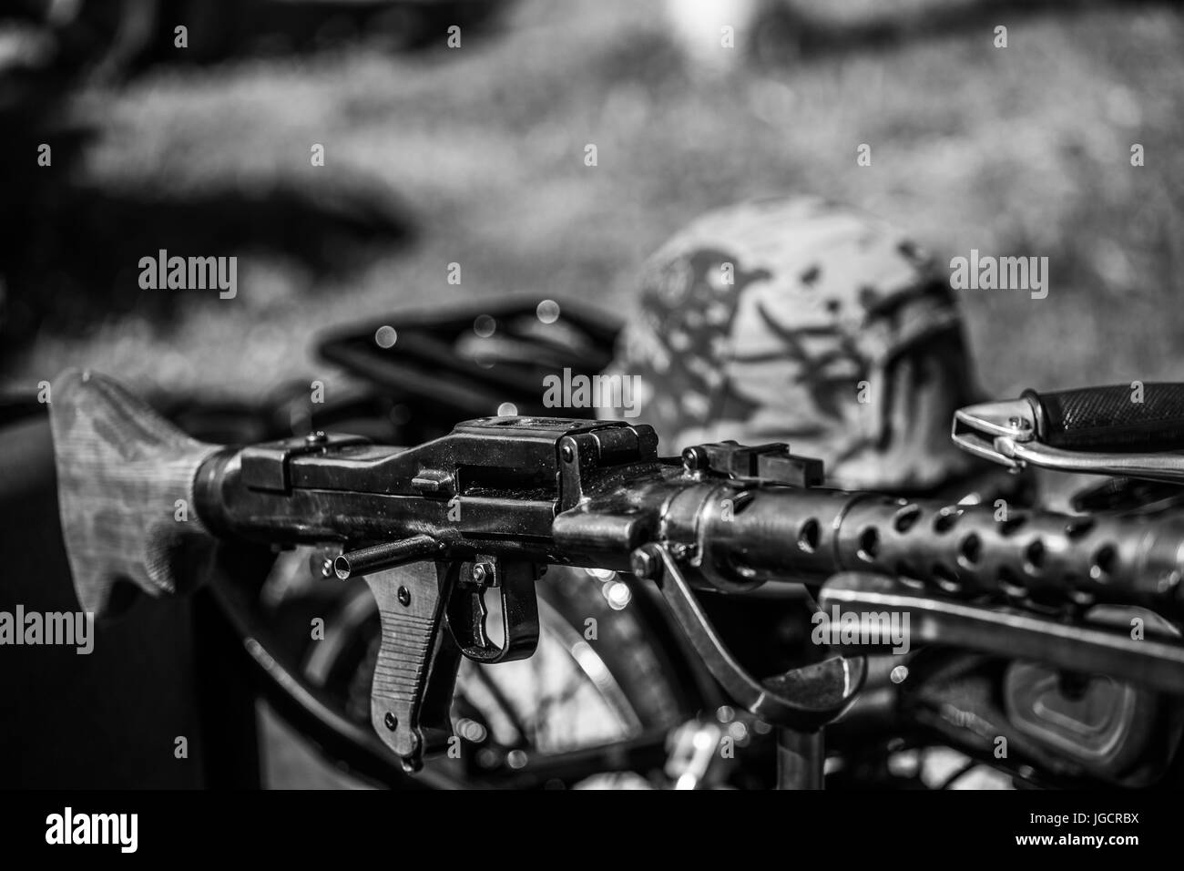 Rifle (Toy) on an old motorcycle BMW R71 from world war after renovation with military cap in the background. Black - Stock Image