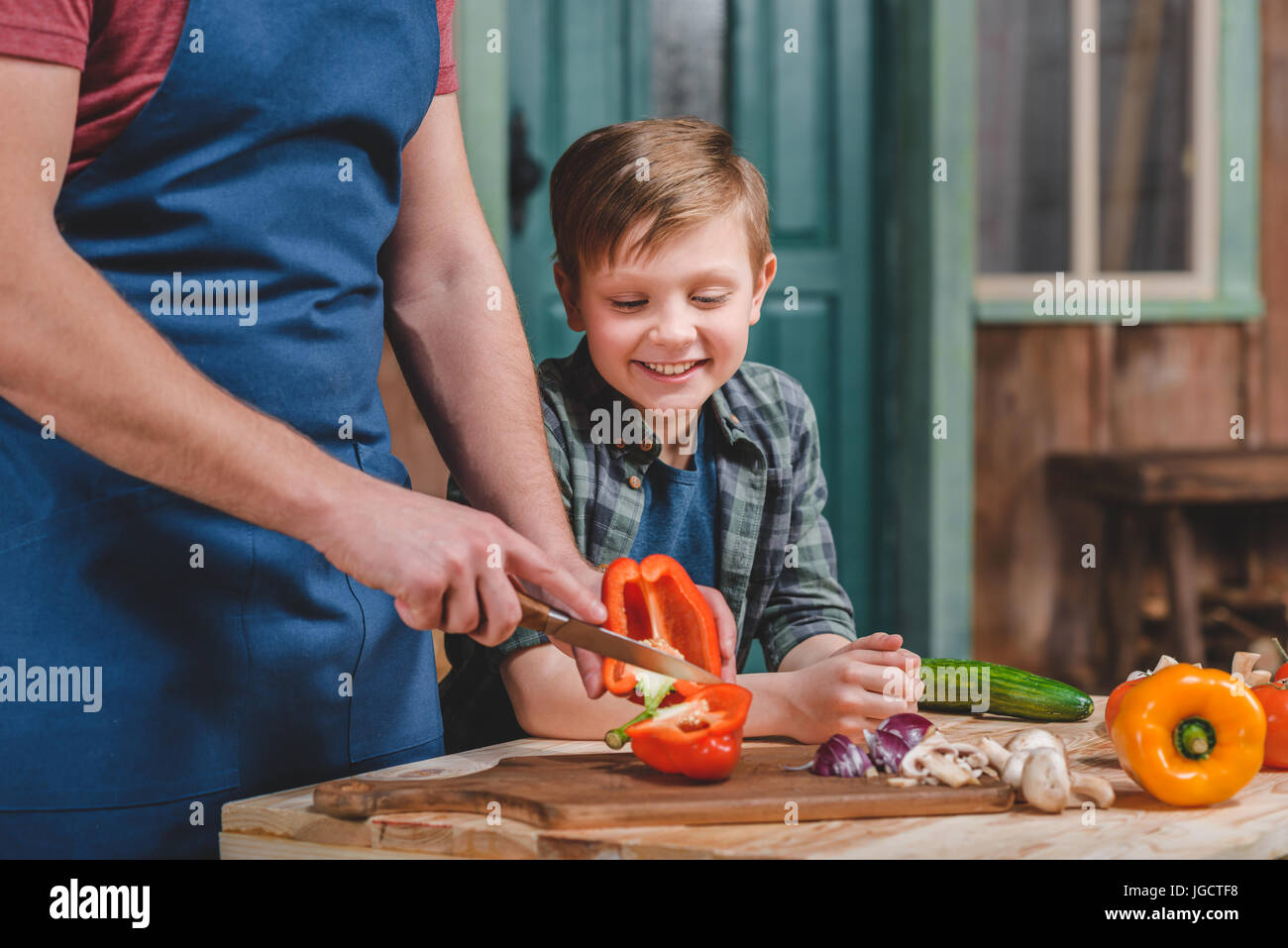 Cute little boy looking at father cutting vegetables on cutting board, dad and son cooking concept - Stock Image