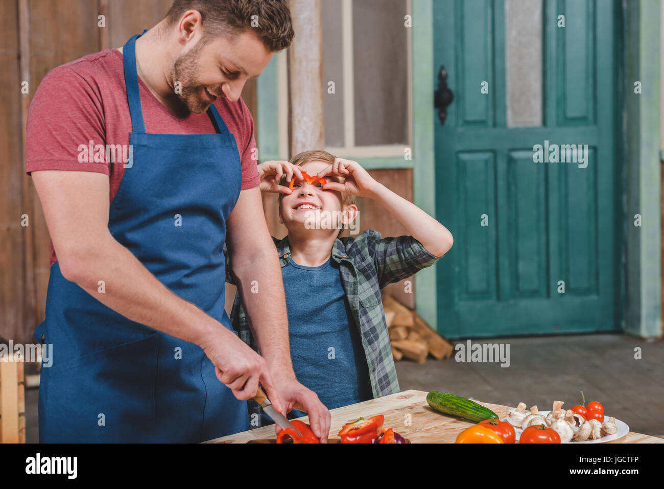Smiling little boy looking at happy father cutting vegetables on cutting board, dad and son cooking concept - Stock Image