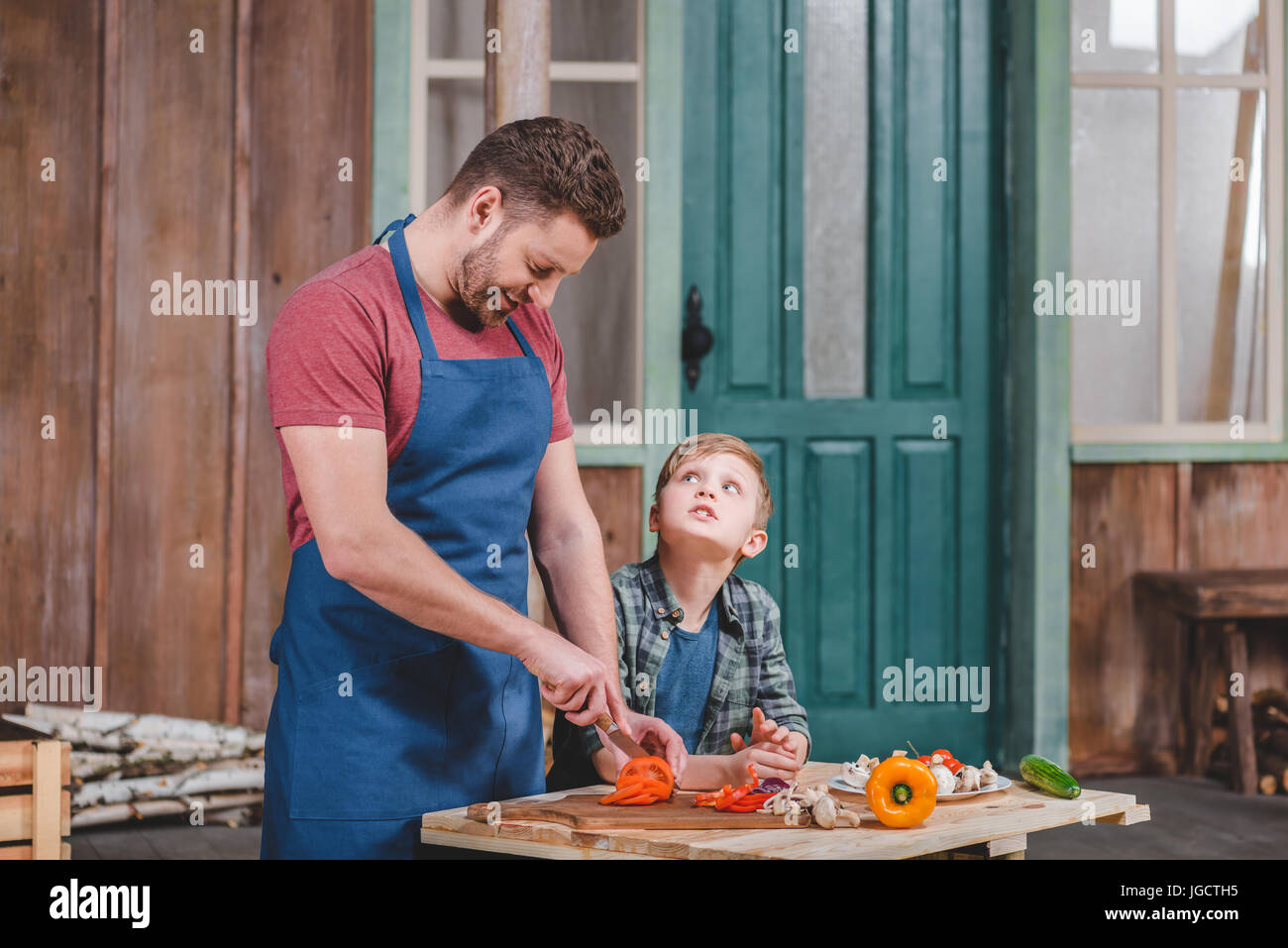 Smiling father and son cutting fresh vegetables at backyard, dad and son cooking concept - Stock Image