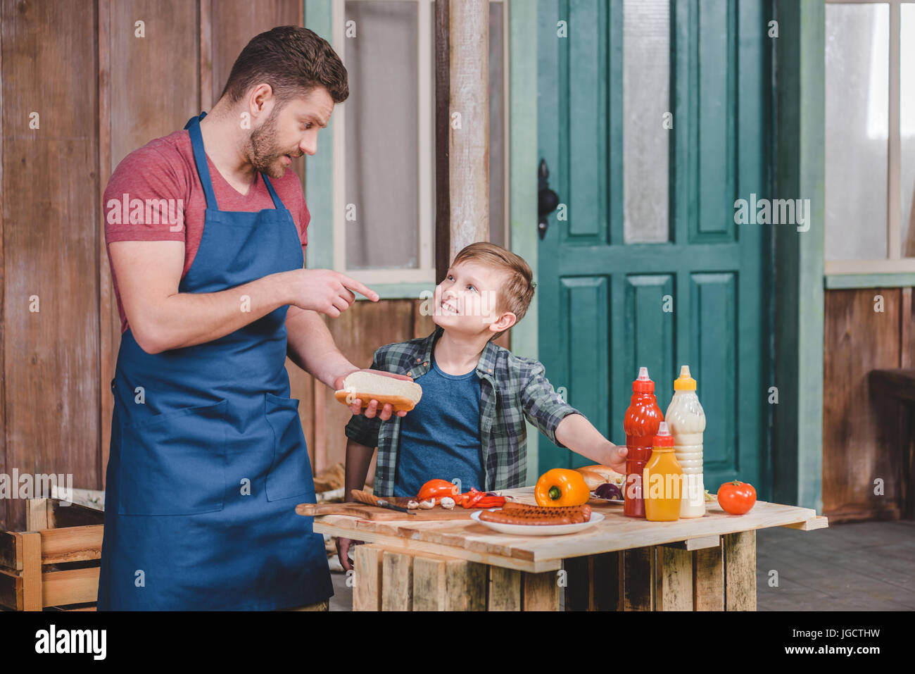 Cute little boy with father in apron preparing hot dog together in backyard, dad and son cooking concept - Stock Image