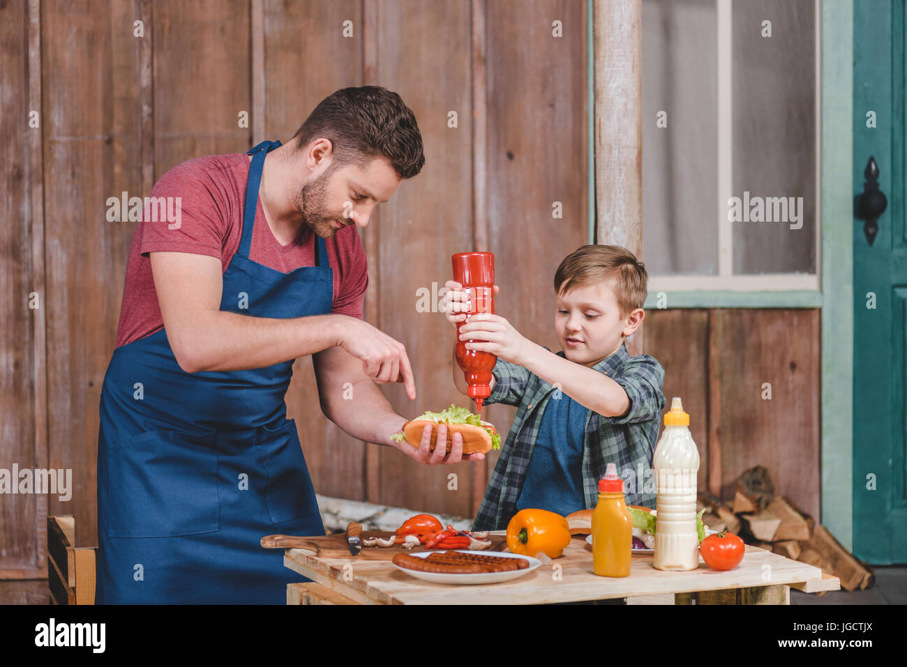 Smiling little boy with father cooking hot dog at backyard, dad and son cooking concept - Stock Image