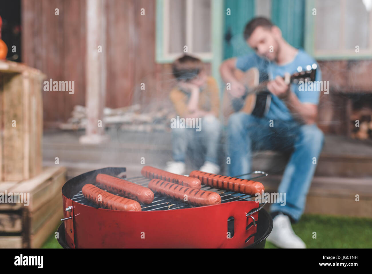 hot dog sausages on grill with family spend time together behind - Stock Image